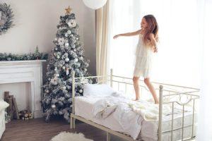 Kind springt auf dem Bett neben einem Weihnachtsbaum