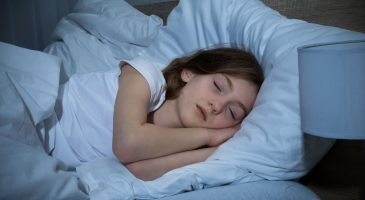 Mädchen schläft im dunklen Schlafzimmer
