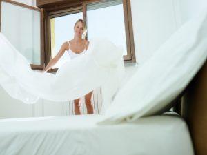 Frau schüttelt Bettwäsche